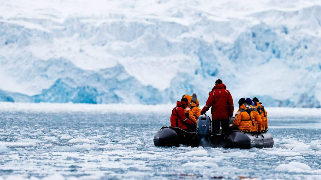 adventure travelers on the spitsbergen in depth small ship cruise trip in a zodiac skiff on icy water with an iceberg in the distance