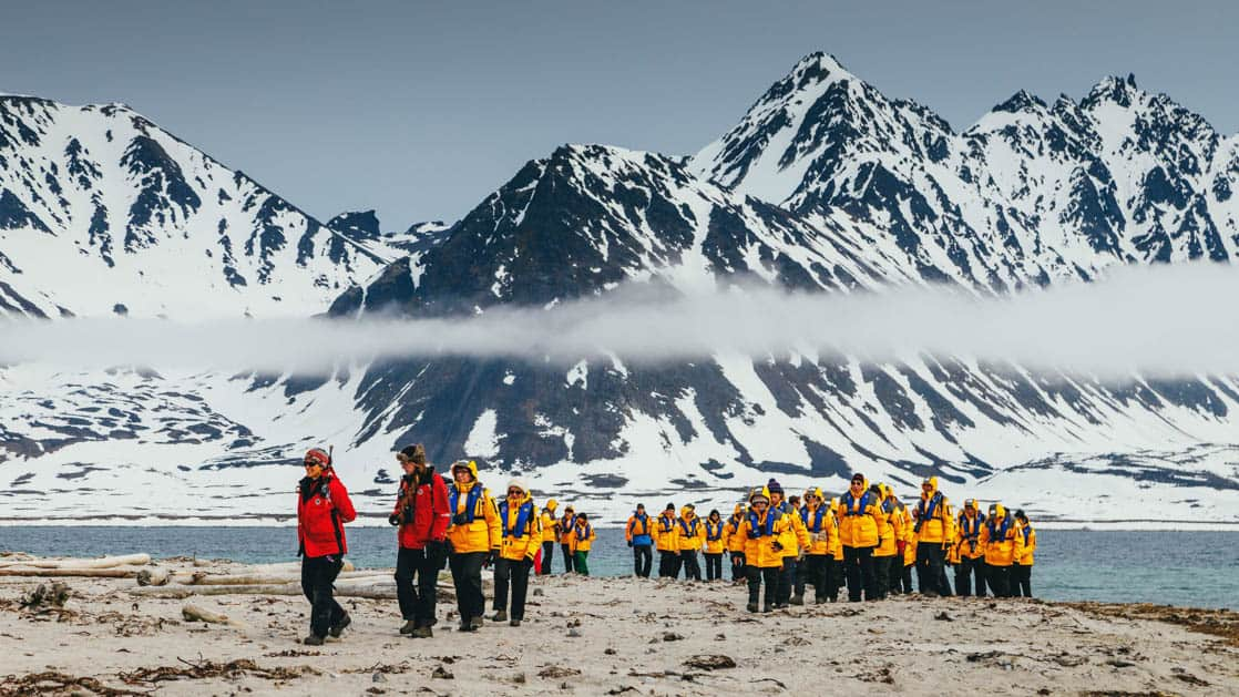 group of travelers with yellow jackets led by two guides in red on a shore excursion of the spitsbergen explorer arctic small ship cruise trip