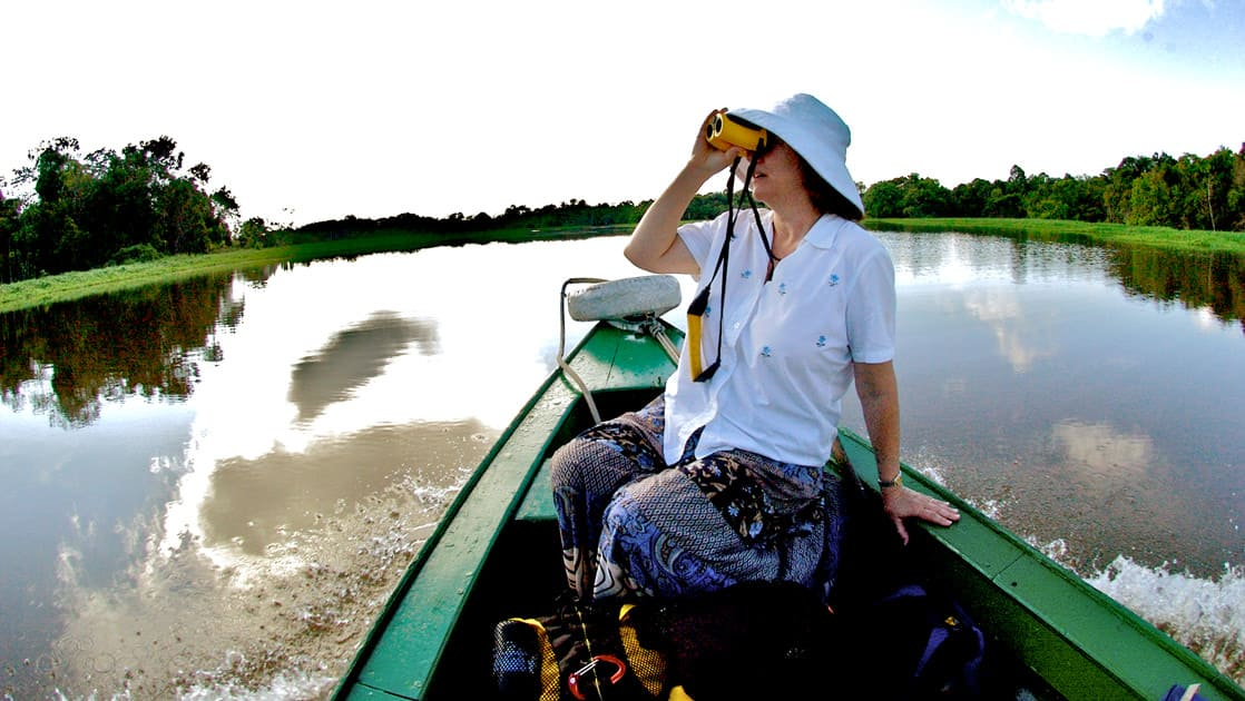 Woman on a canoe on a calm river in brazil with binoculars looking for wildlife