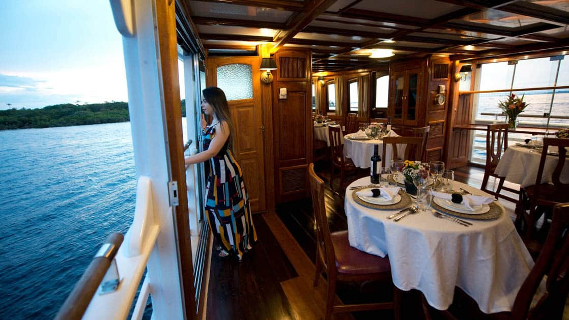 Female looking out open deck in salon dining room aboard Tucano.