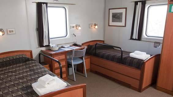 Superior Twin cabin aboard Ushuaia with desk and two twin beds.