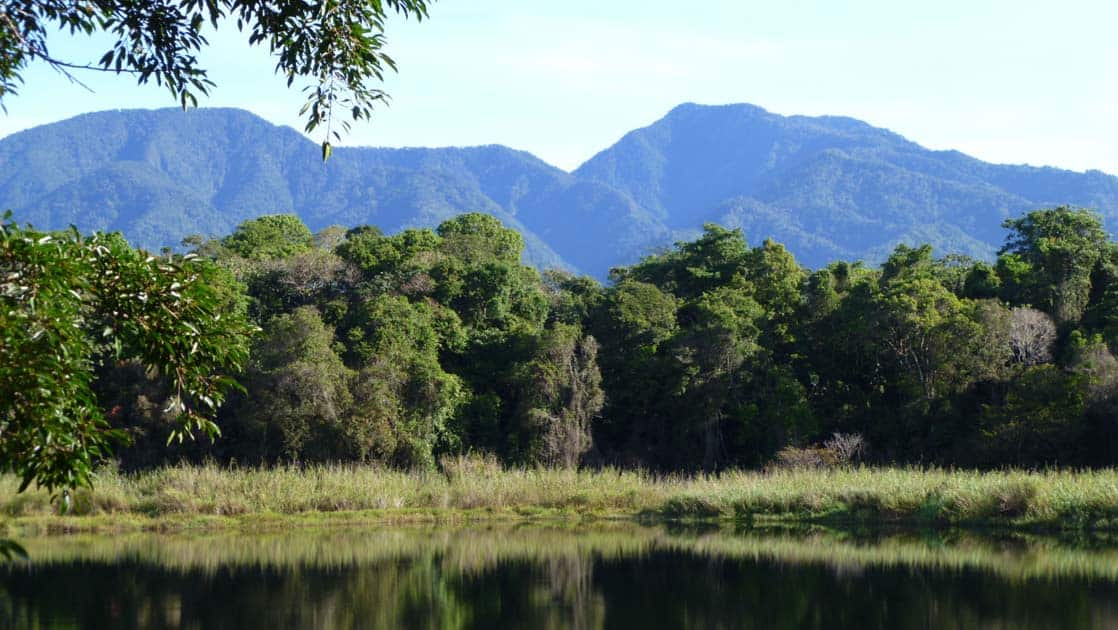 A scene of blue mountains and a green lagoon in Panama.