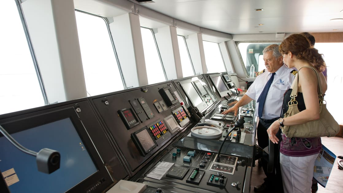 Officer showing a guest the navigational equipment on the bridge aboard Varitey Voyager.aboard Varitey Voyager.