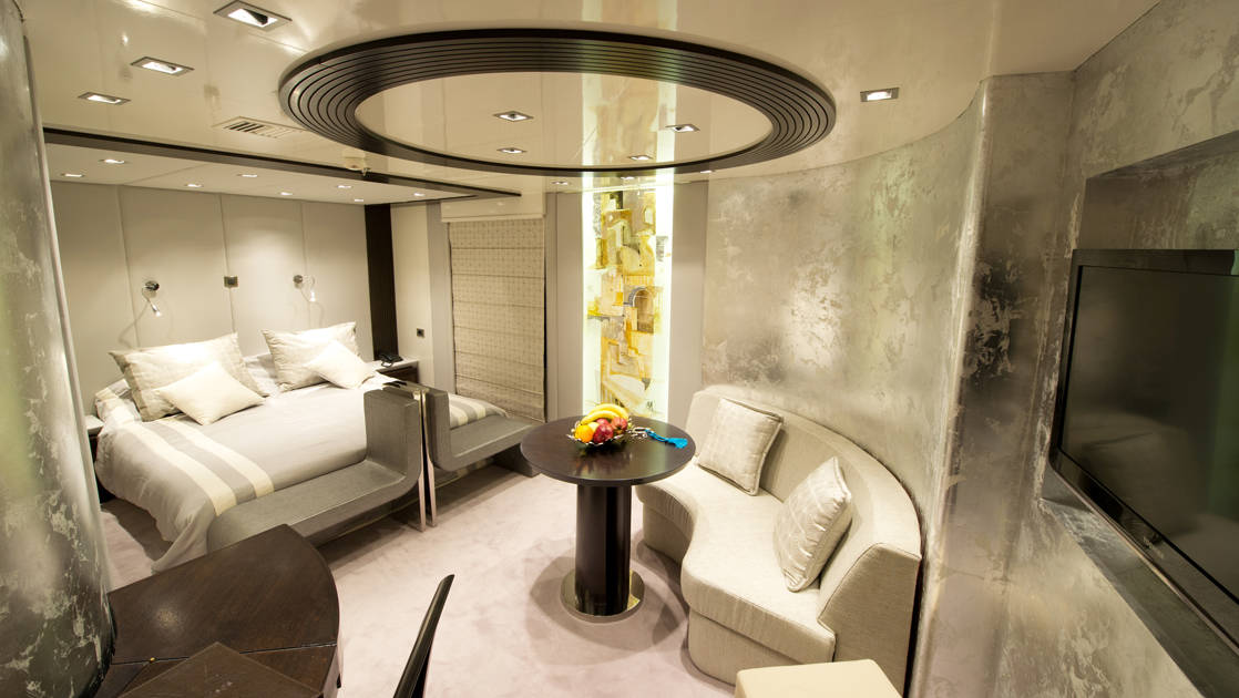 Owner's Suite with bed, sitting area, and tv aboard Variety Voyager.