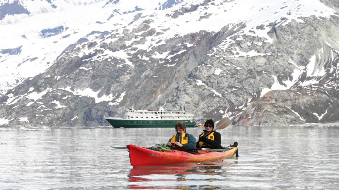 Couple kayaking in front of Wilderness Explorer by snowy fjords.
