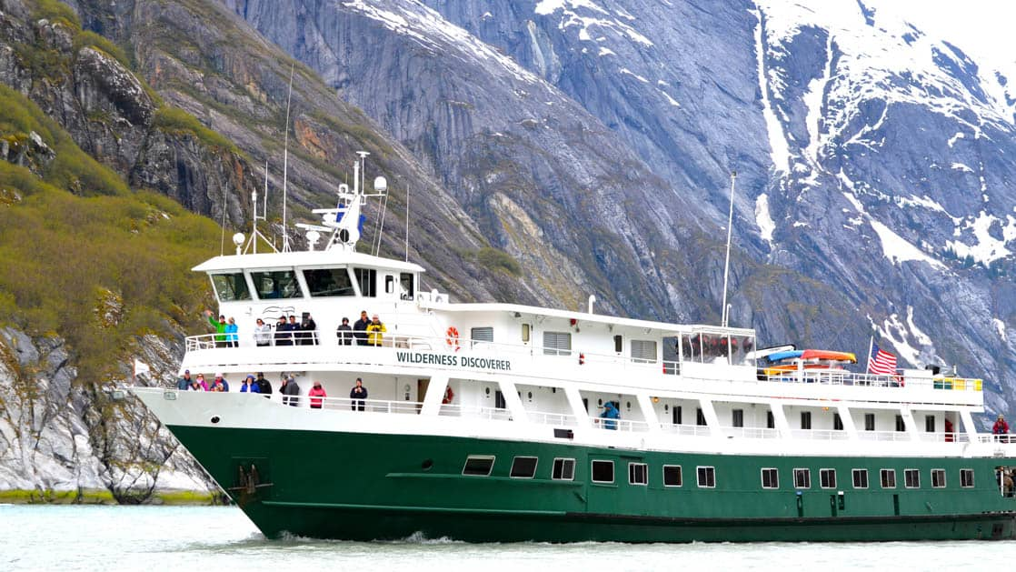 Portside exterior view of Wilderness Discoverer cruising in Alaska.