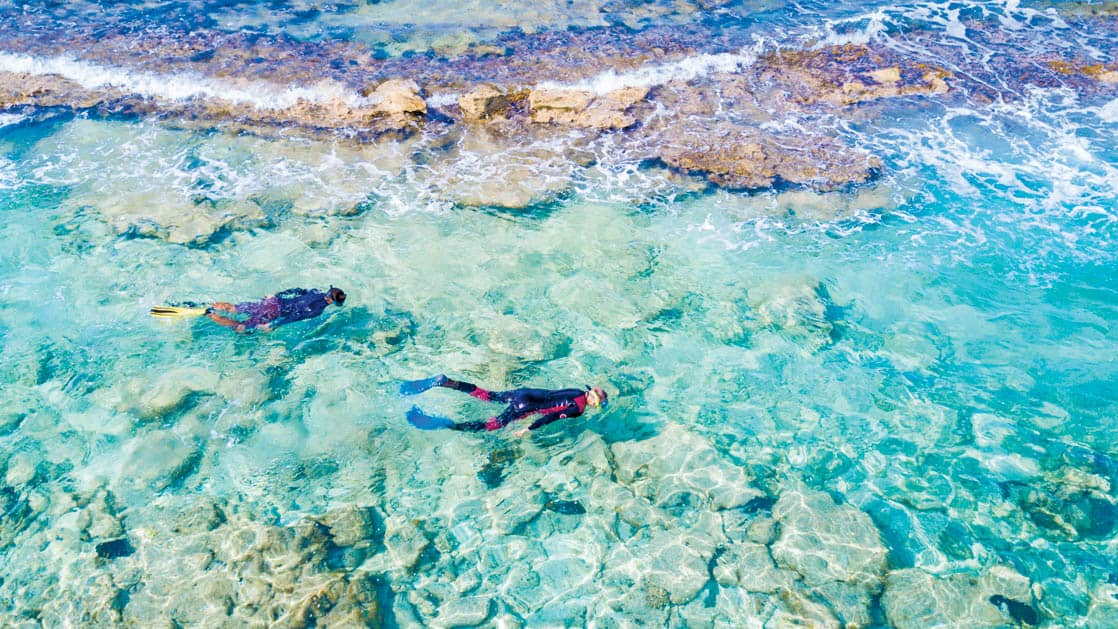 Aerial view of two people snorkeling in the shallow reef and clear blue waters of Half Moon Caye Belize