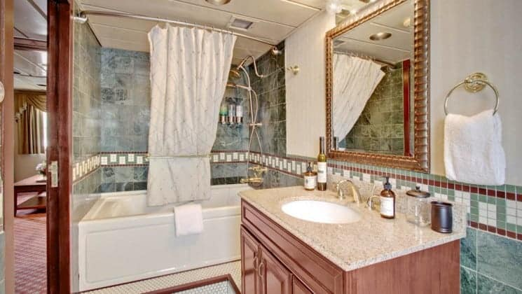 Bathroom with tub/shower, sink, mirror aboard Wilderness Legacy expedition ship