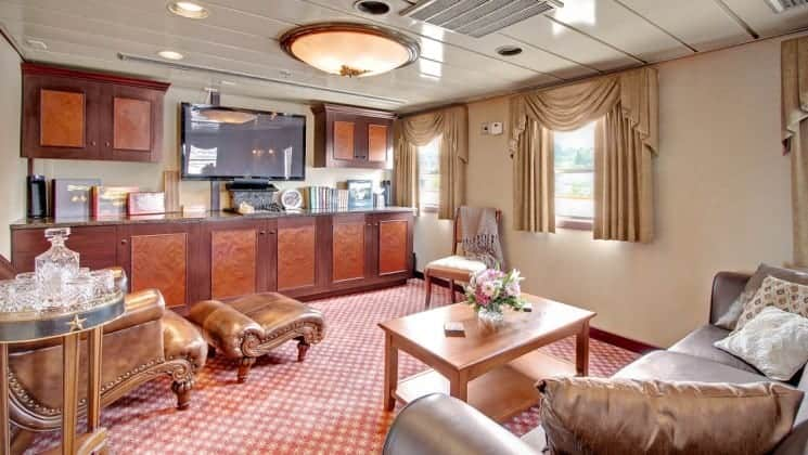 Suite living room with couch, chairs, table, TV, windows aboard Wilderness Legacy expedition ship