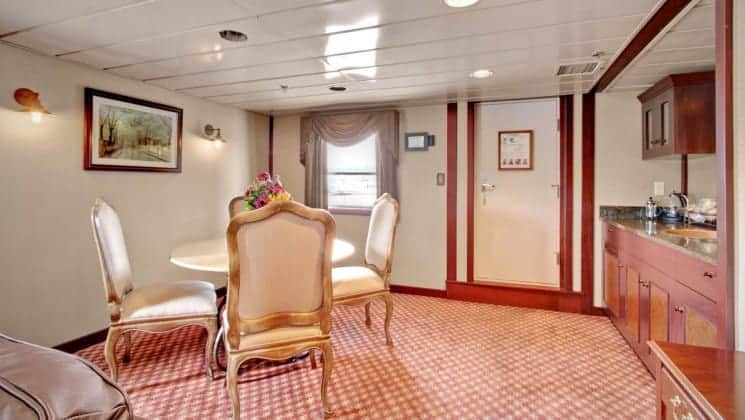 Dining table with four chairs near bar in suite aboard Wilderness Legacy expedition ship