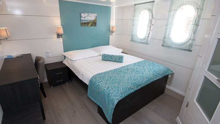 Cabin aboard Admiral with double bed and windows.