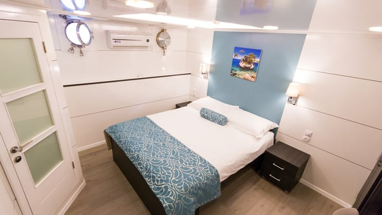 Cabin aboard Admiral with double bed and portholes.