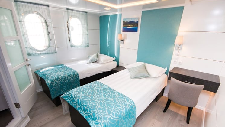 Cabin aboard Admiral with two twin beds and windows.