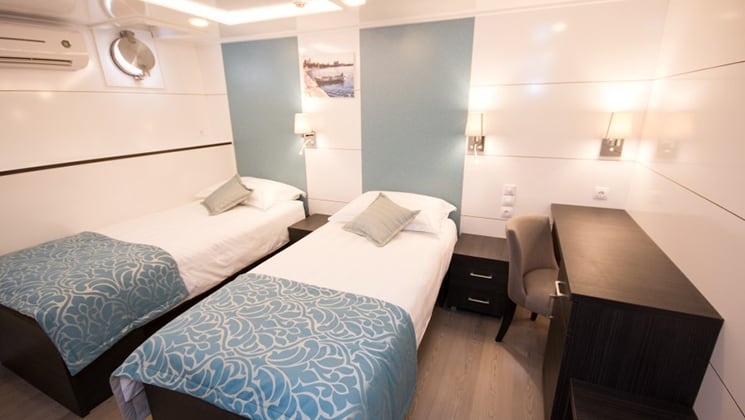 Cabin aboard Admiral with two twin beds and portholes.