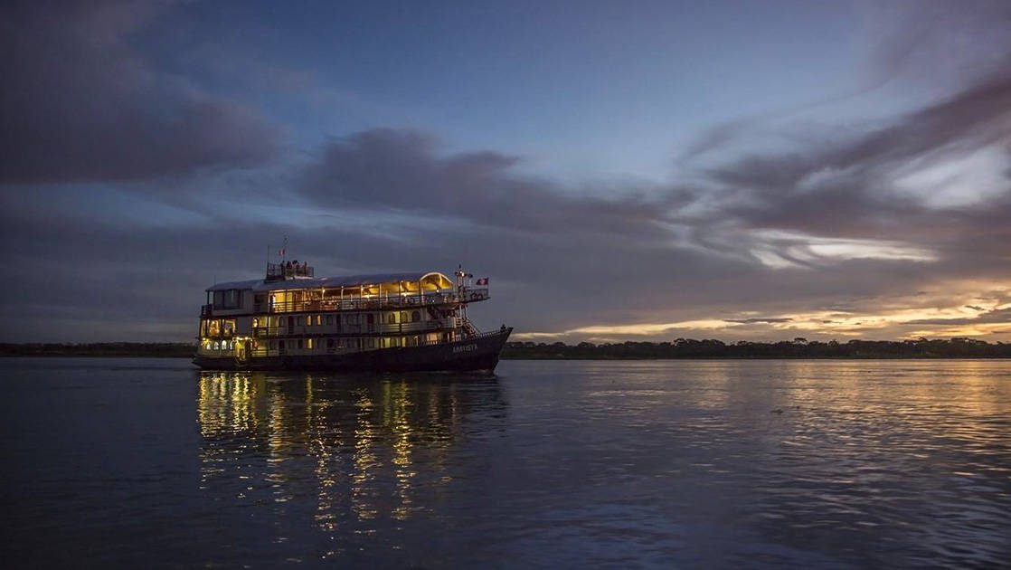 Amatista small ship cruising in the evening on the Pervuian Amazon.