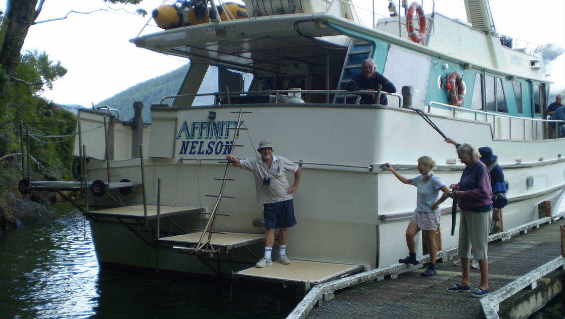 Stern of the Affinity docked with people posing.