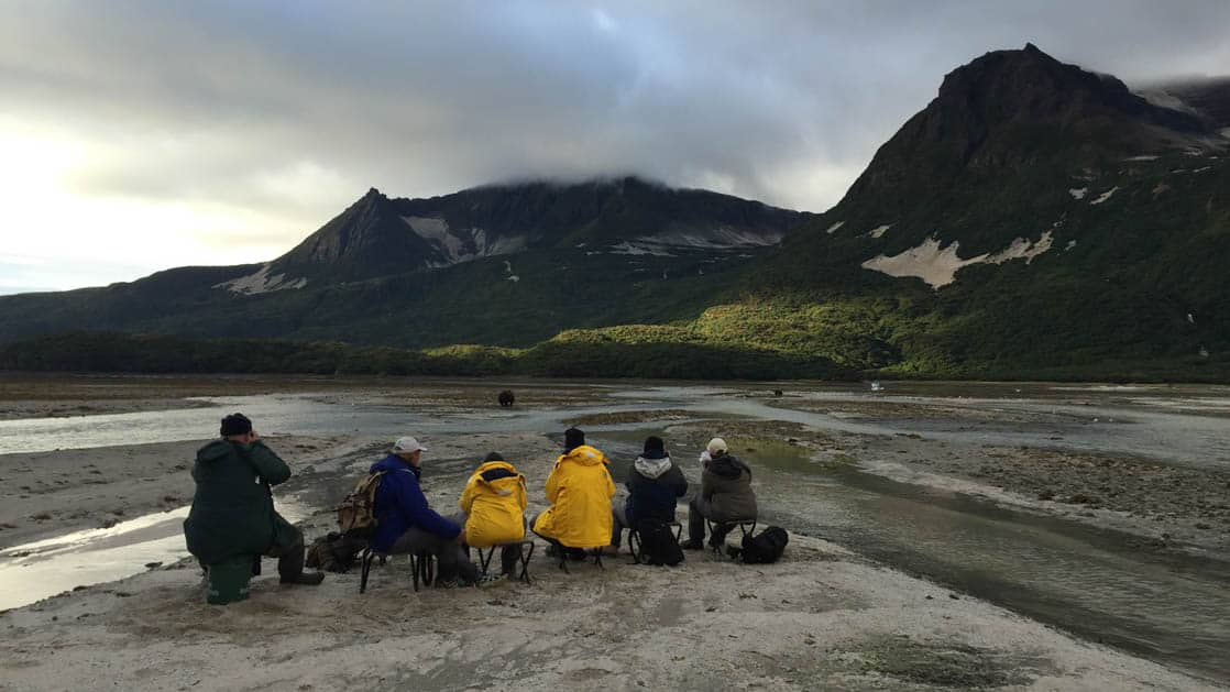 A group of small ship passengers sitting on the beach in Alaska during sunset and taking pictures