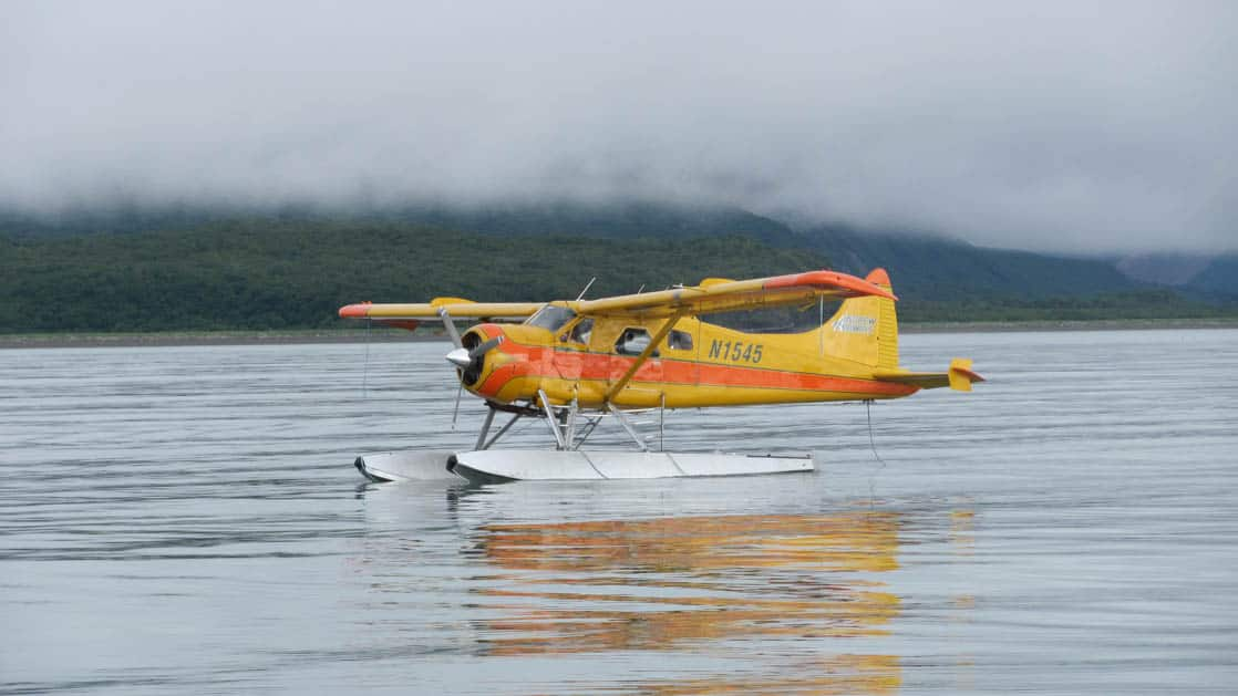 Yellow float plane on the still water in Alaska with low clouds.