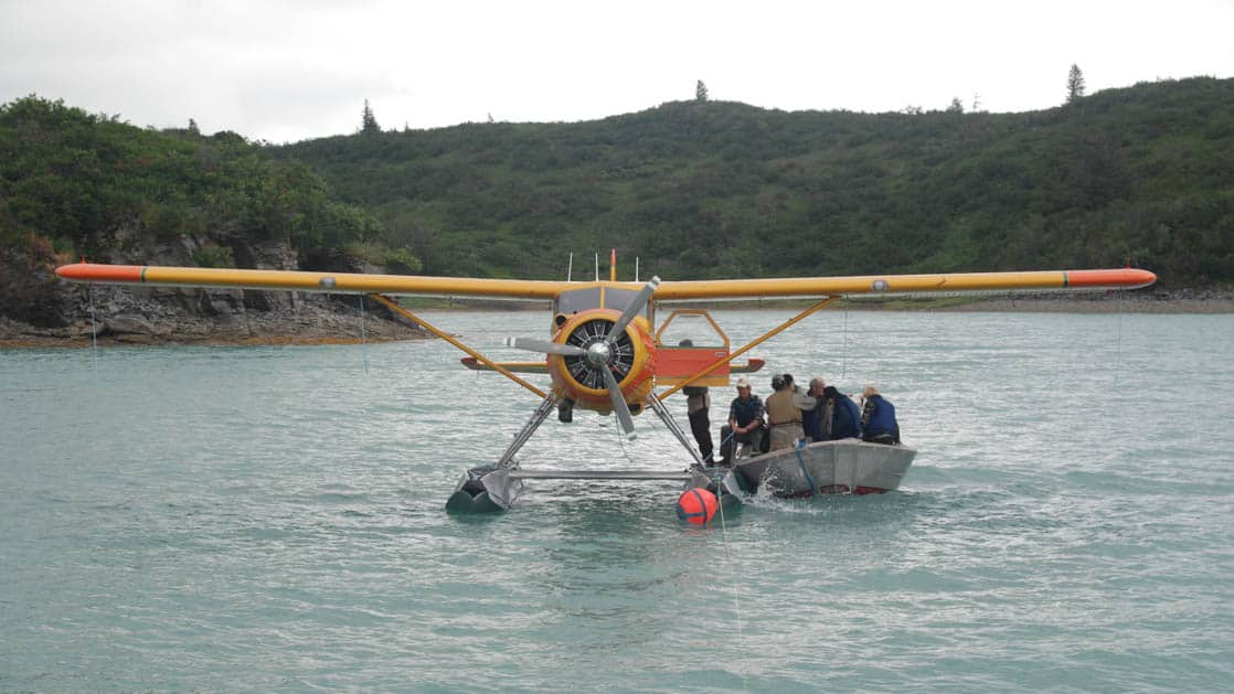 A floatplane in the water with a skiff full of people getting off the plane in Alaska