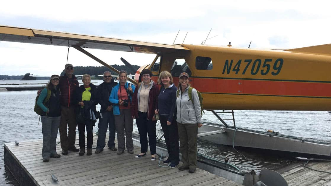 Float plane docked in Alaska with its group of passengers posing in front.
