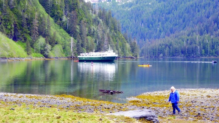 hiker on the alaska fjords and glaciers cruise on shore with a small ship anchored in the background