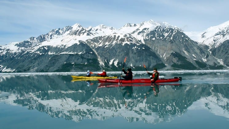 4 adventure travelers in 2 kayaks on calm alaska waters in glacier bay national park with mountains in the background