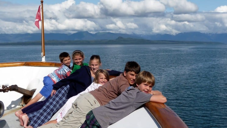 a group of kids relaxing on the bow on a sunny day with mountains in the background on the alaska fjords and glaciers small ship cruise