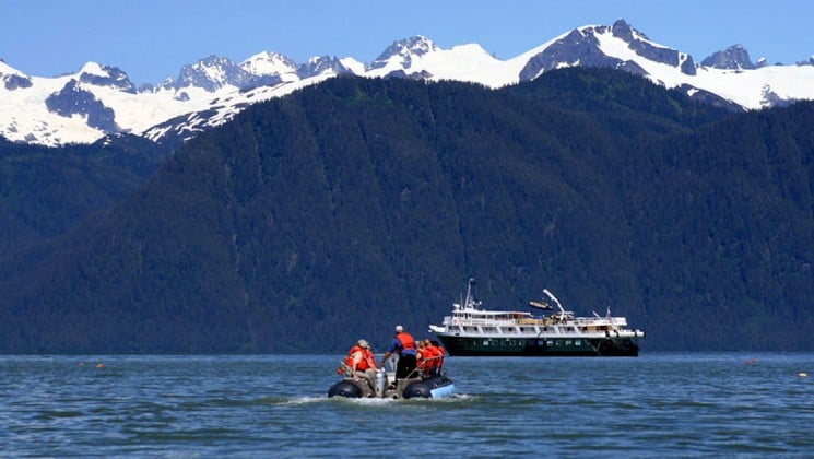 adventure travelers on a zodiac skiff going toward a small ship in alaska glacier bay national park on a sunny day