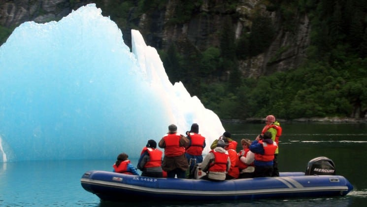 a group of travelers in a skiff in glacier bay national park alaska looking at and taking pictures of a piece of floating ice