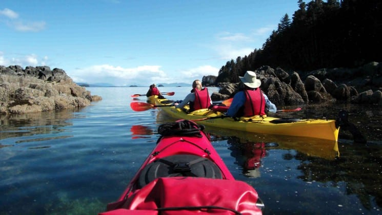Three kayakers paddling through a narrow rocky channel in Alaska