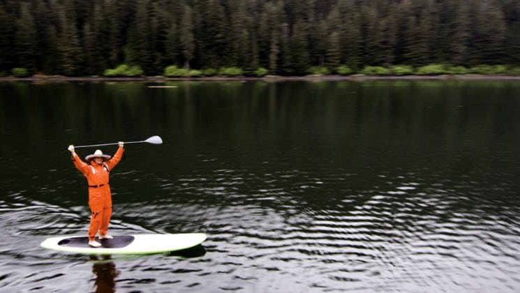 standup paddle boarder wearing a dry suit and raising his oar in alaska