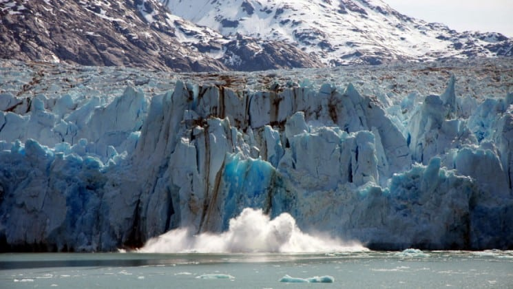Giant blue glacier calving with a big splash on an Alaska Islands, Whales and Glacier cruise.