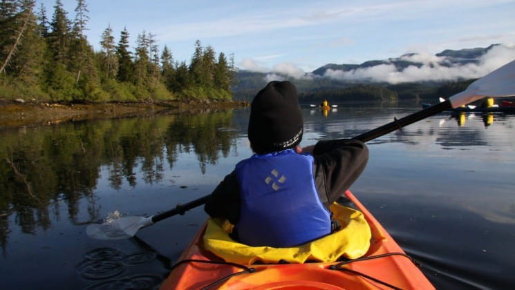A child kayaking along the tree-lined shore on an Alaska cruise