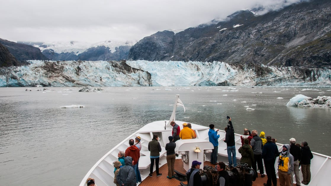 Passengers on the bow of a small ship in Alaska as they approach a glacier.