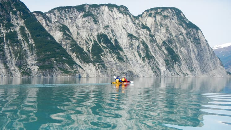 Two people in a kayak paddling in the Alaskan fjords