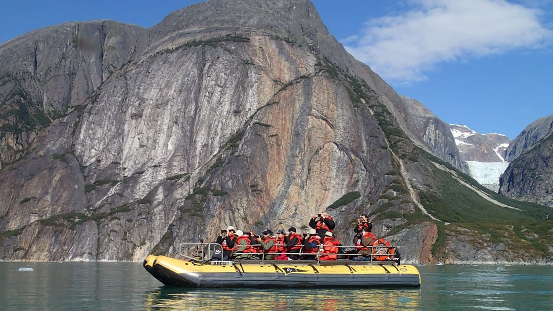 Skiff with small ship cruise passengers going through a fjord in Alaska.