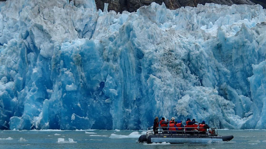 Skiff with small ship cruise passengers up close to the face of a blue glacier in Alaska