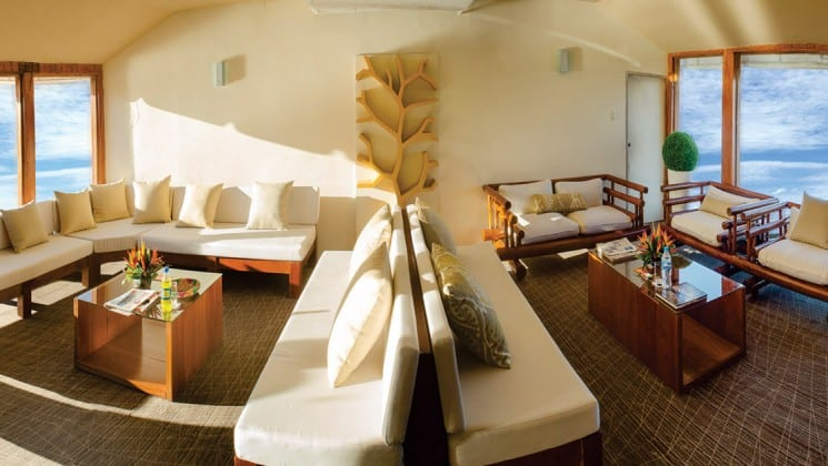 Lounge aboard Amatista with white couches, large windows and small tables.