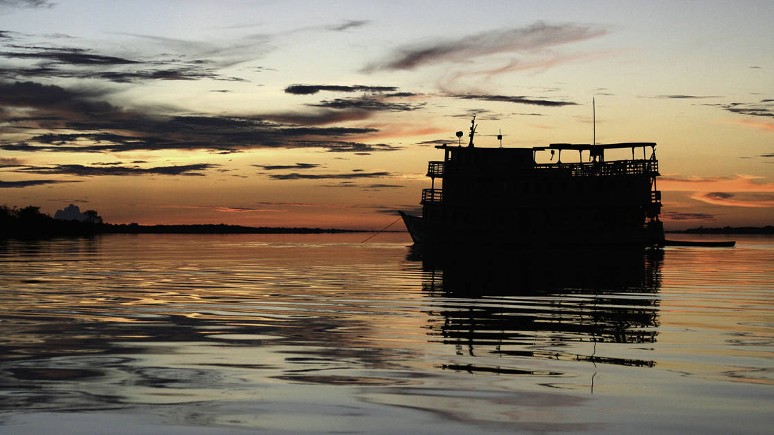 silhouette of the tucano small ship cruising on the rio negro in brazil during sunset
