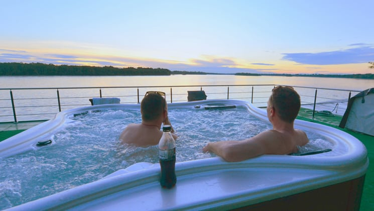 Two guests in the hot tub looking at the sunset on the top deck aboard Anakonda.