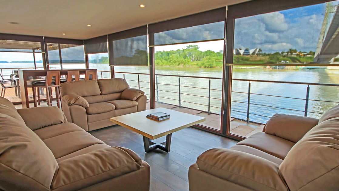 Sitting area and lounge by floor to ceiling windows aboard Anakonda.
