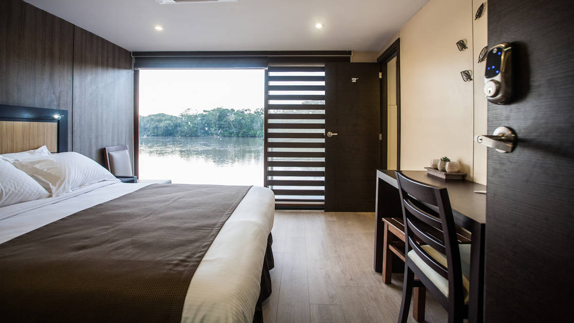 Standard Suite aboard Anakonda with large bed and large window.