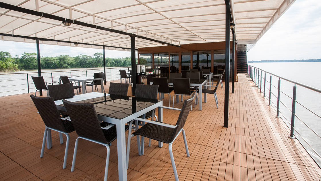 Top covered deck with chairs and tables aboard Anakonda.