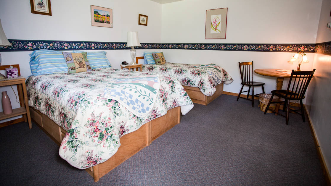 Annie Mae Lodge room with two queen beds with white quilts and a table and chairs.