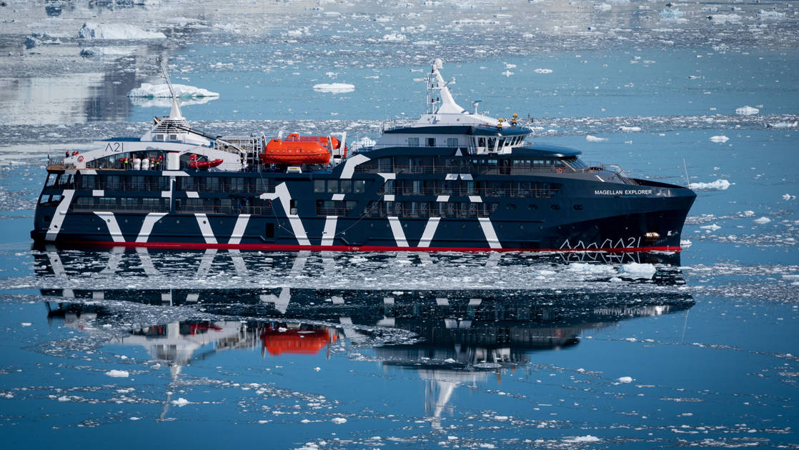 Exterior starboard side of dark navy blue Magellan Explorer Antarctica expedition ship floating on icy reflective ocean line