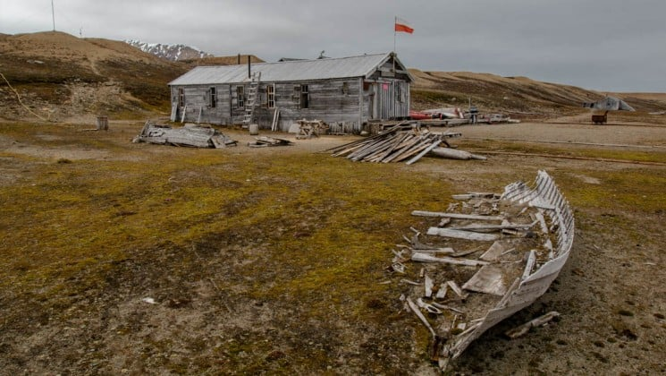 dilapidated boat and wooden house near svalbard on arctic wildlife safari cruise