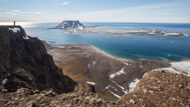 mountaintop view of arctic waters and large island near svalbard on clear day