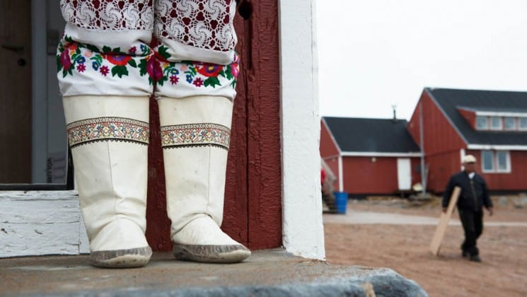 local woman in native boots outside her home near svalbard on arctic wildlife safari cruise
