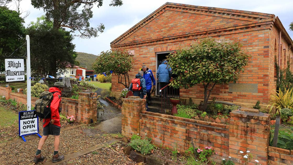 a traveler in a red jacket enters the bligh museum in tasmania australlia, a red brick building with trees and bushes around it