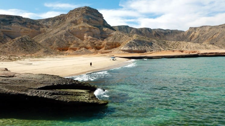 distant beach with turquoise waters and surrounding mountains in baja